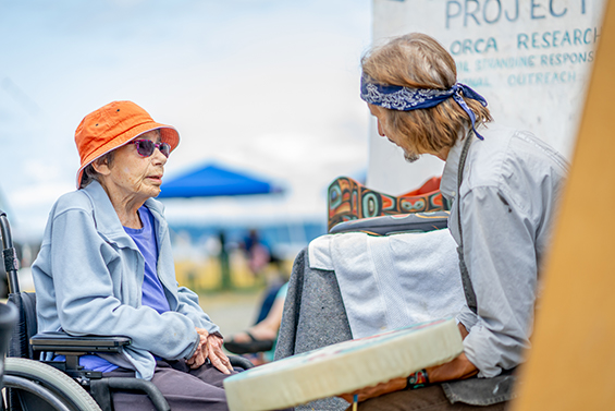 Senior citizen visits with an art vendor at a local Vashon, WA market