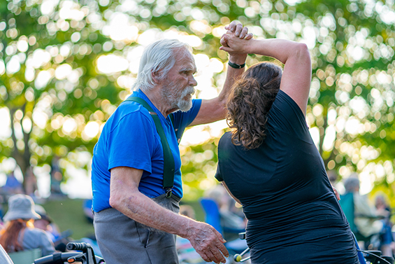 Resident of senior living community dances with a younger woman